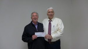 Jim Grimes representing KOC (Knights of Columbus) is shown giving a generous check for the SARC to Sam Beggs