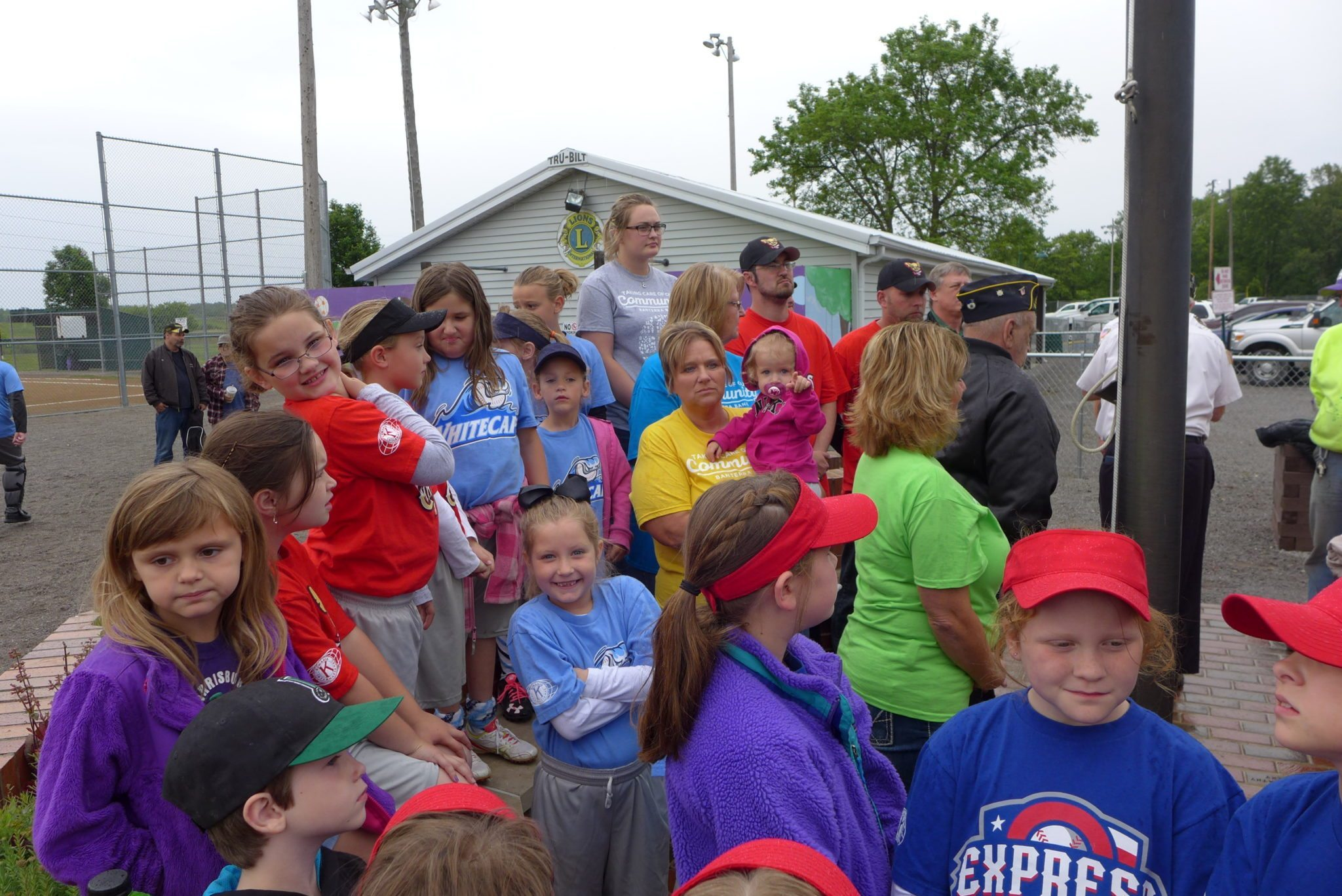 Banterra Employees, ball players and parents watch the flag folding.